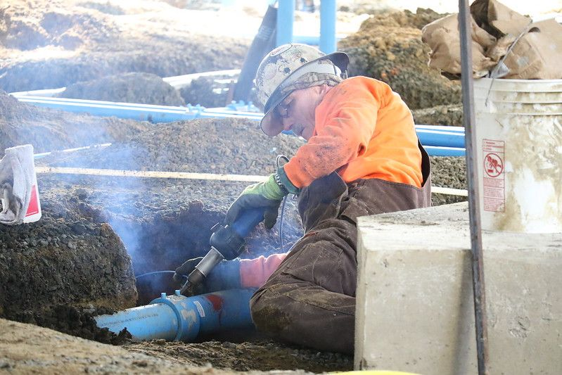 construction worker fitting pipes together in a foundation