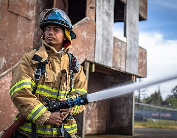 Fire Science student using s fire hose during a training program