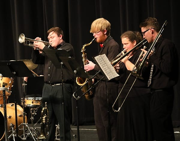 Three men and one woman performing in a band concert on campus