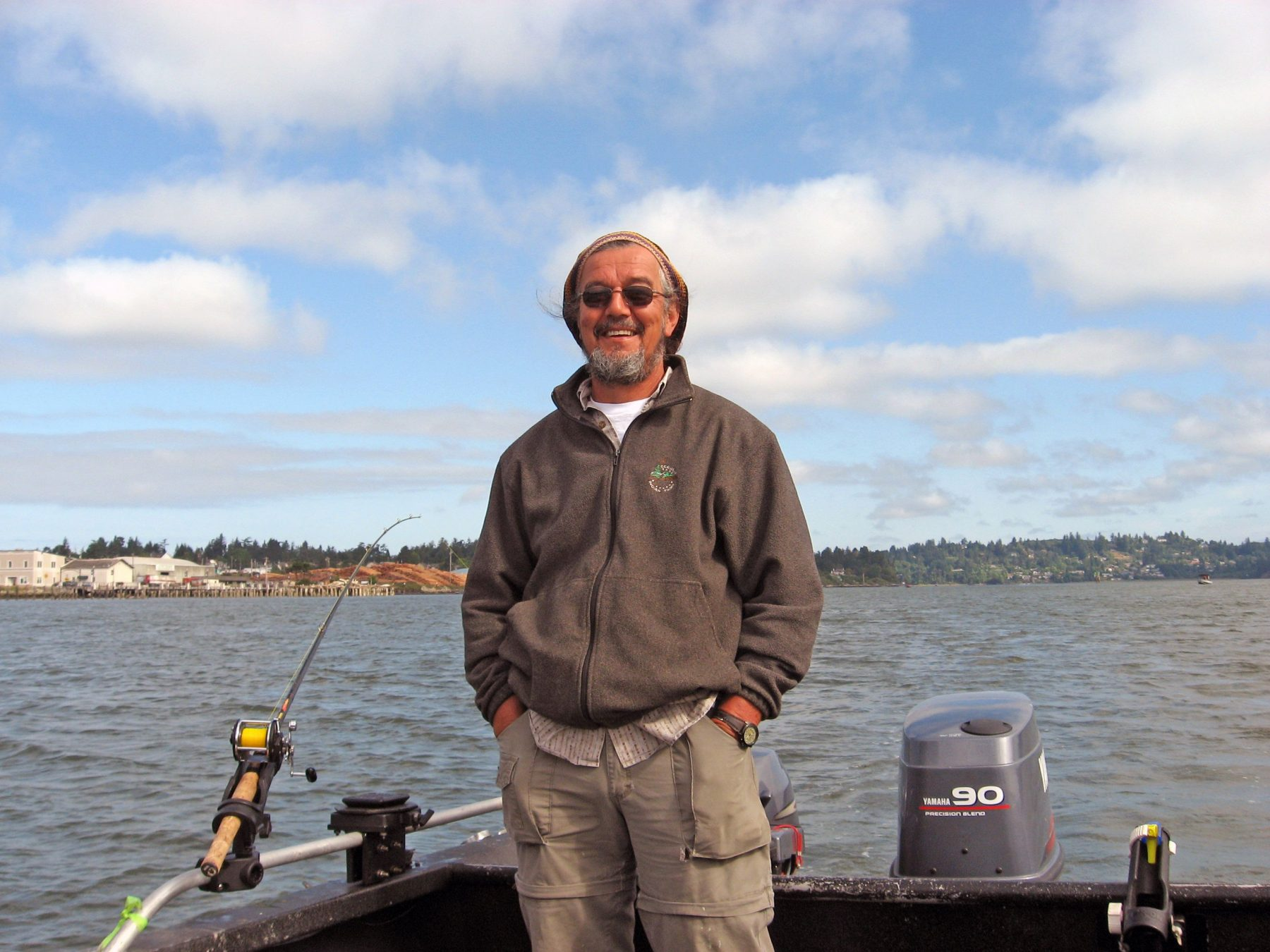 photo of a man standing on a fishing boat smiling