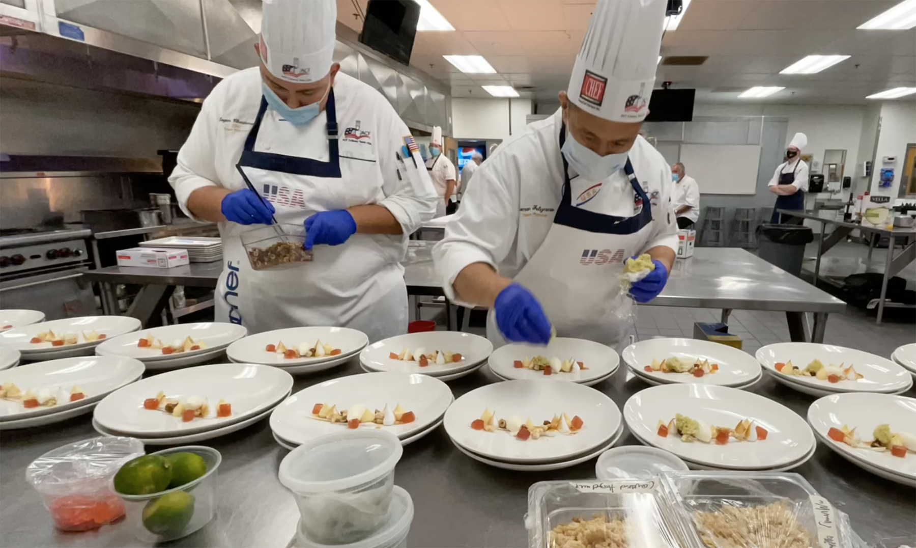 two chefs in kitchen with numerous plates in front of them