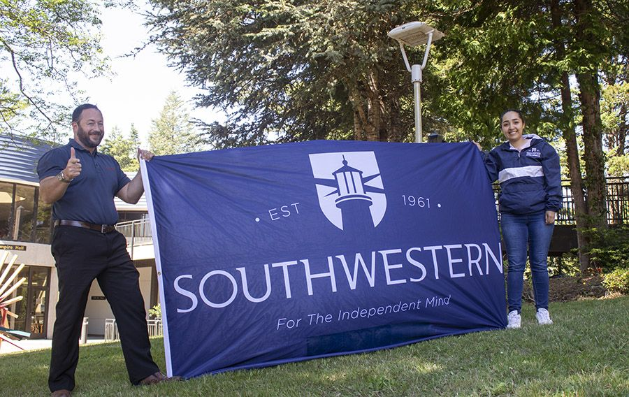two people outside holding up a banner with the school logo on it