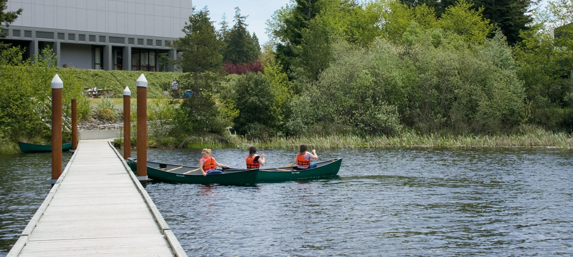 Three female students canoeing on the Beautiful Empire Lakes
